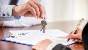 Person handing over keys to new home